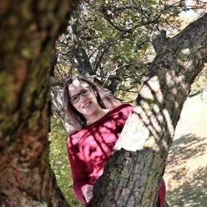 Junge Frau sitzt in einem Baum. Energetische Begleitung stellt immer auch eine Verbindung zur ursprünglichen Natur von Mensch und Tier her.
