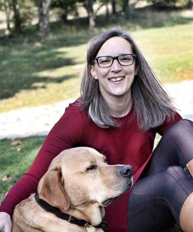 Junge Frau sitzt mit ihrem Hund am Boden und lächelt in die Kamera. Energetische Arbeit trägt zum besseren Verständnis zwischen Mensch und Tier bei.