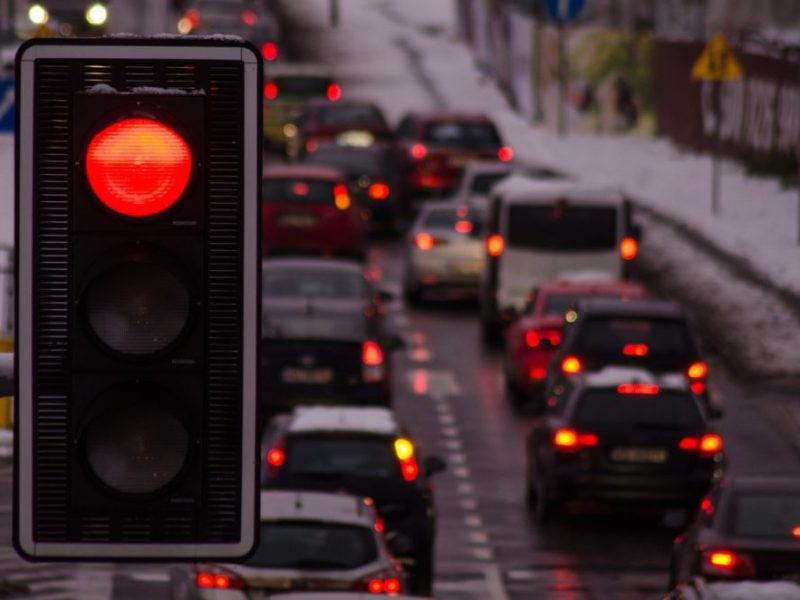 a red traffic light in the foreground with heavy traffic in the background