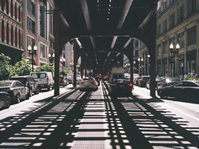 cars drive through the Chicago loop, in the shadows of overhead transit rail lines