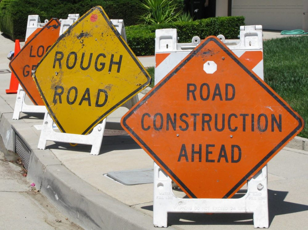 """a trio of warning signs rest on a curb, at right: """"road construction ahead""""; center: """"rough road"""""""
