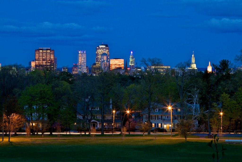 The Hartford, Connecticut skyline rises in the distance, above a row of houses, at dusk