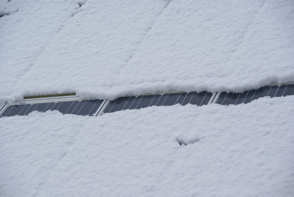 A blanket of snow nearly completely covers a solar array