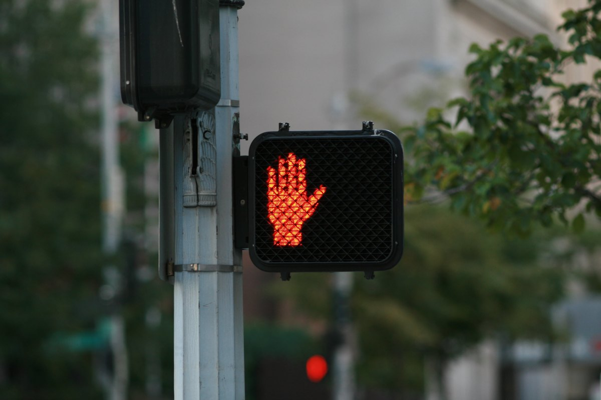 "A pedestrian crossing signal with an illuminated red hand, indicating ""don't walk."""