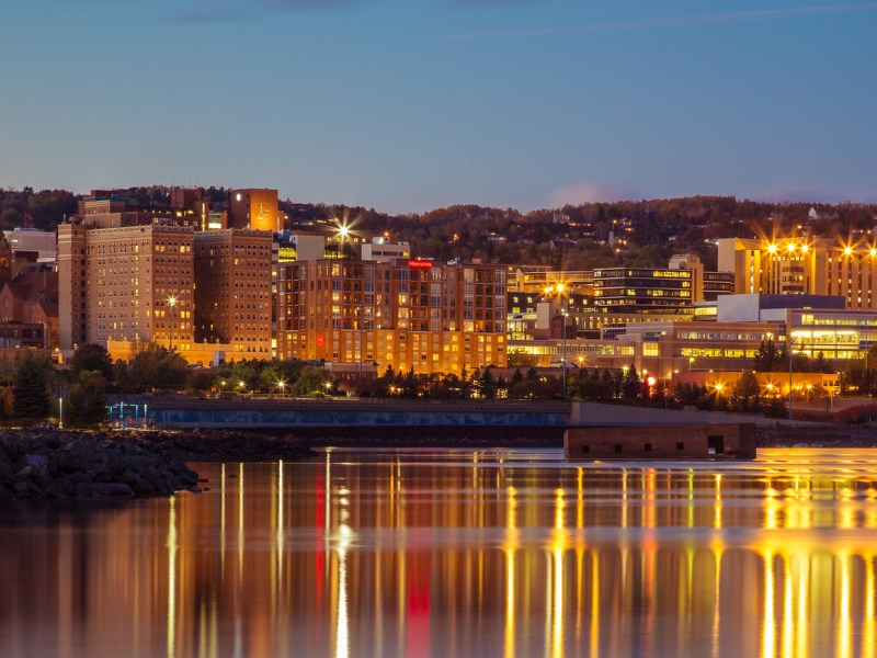 Lake Superior reflects lighted skyline along the Duluth, Minnesota, lakefront.