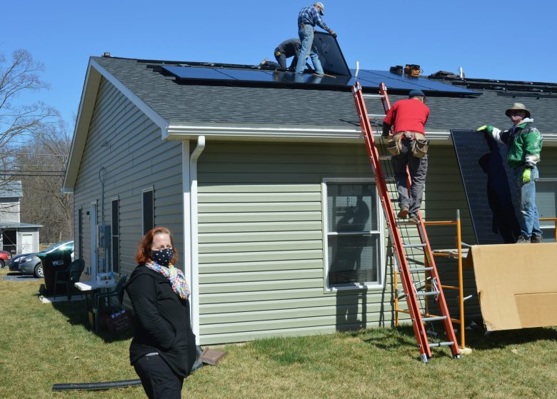 Amber Cox outside her home as installers assemble solar panels on her roof in the background.