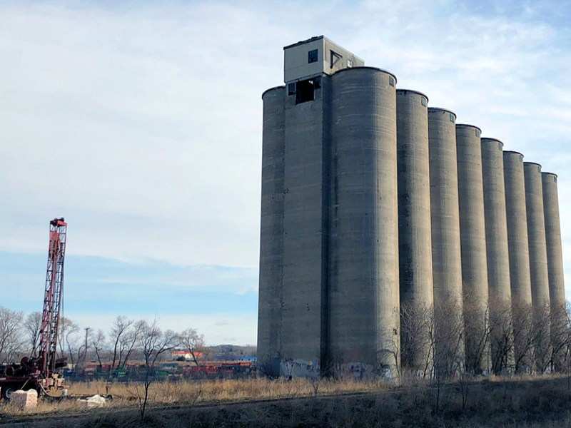 A group of grain silos tower over a drilling rig in Minneapolis.