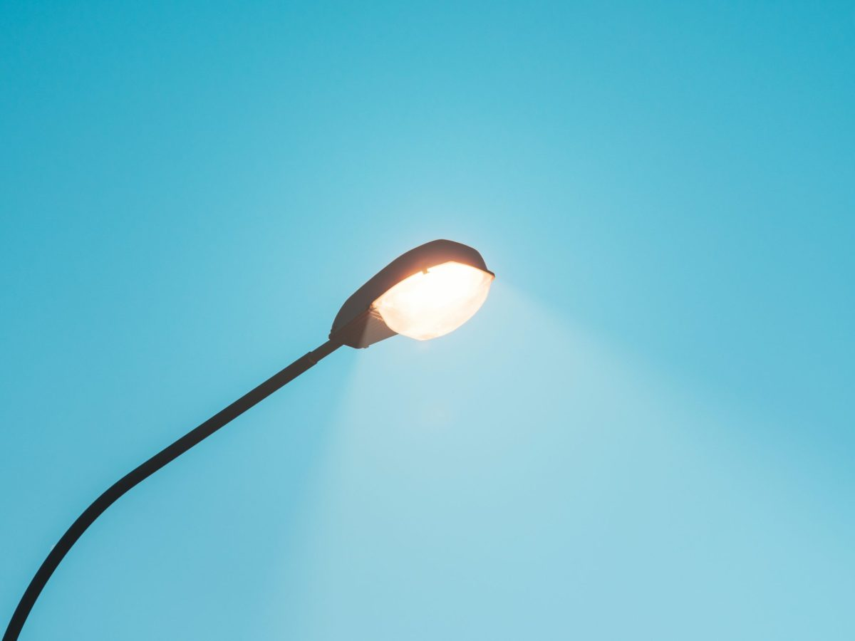 Looking upward at a streetlight with clear blue sky background.