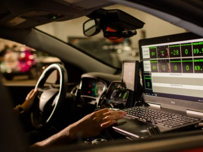 A person sits behind the wheel of a car with a laptop reading out statistics about the car's inner workings.