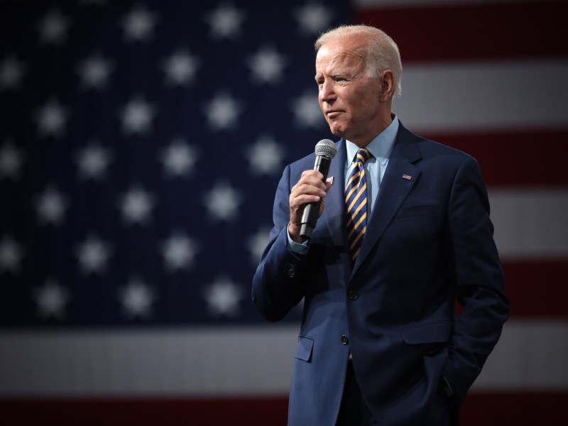 Joe Biden holding a microphone to speak in front of a large American flag.