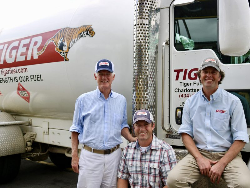 From left, David, Taylor and Gordon Sutton pose in front of a Tiger Fuel-branded semi truck.