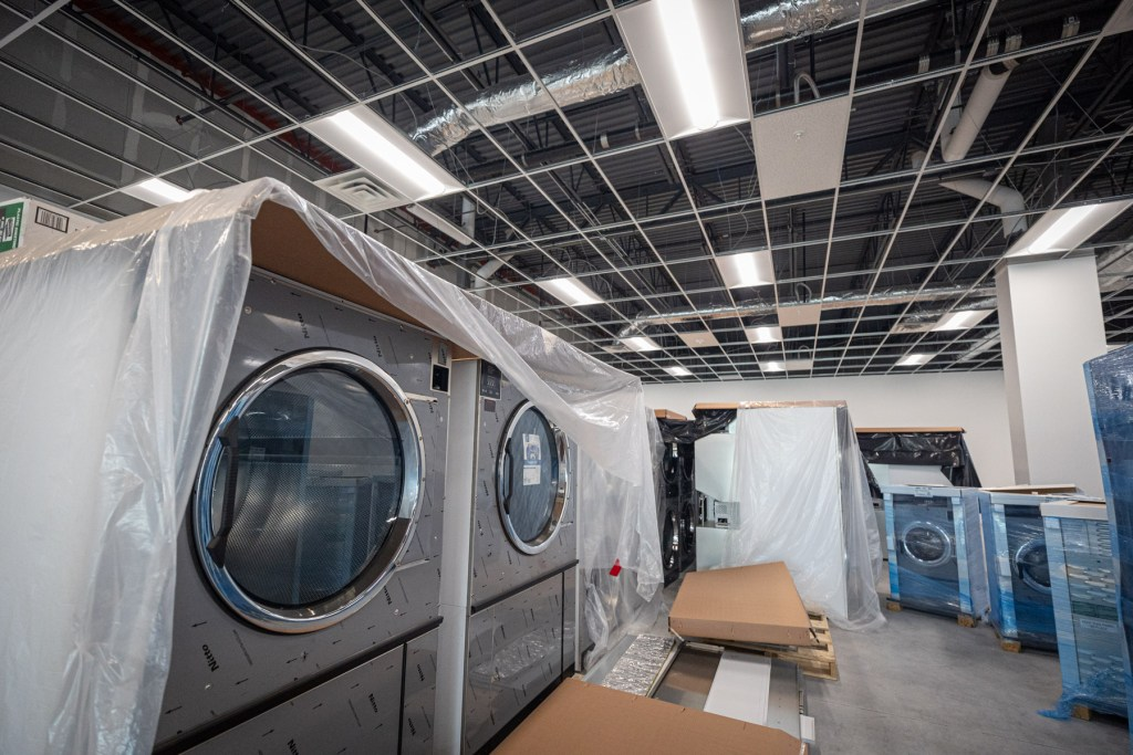New washing machines are covered in tarps and plastic as they await installation.