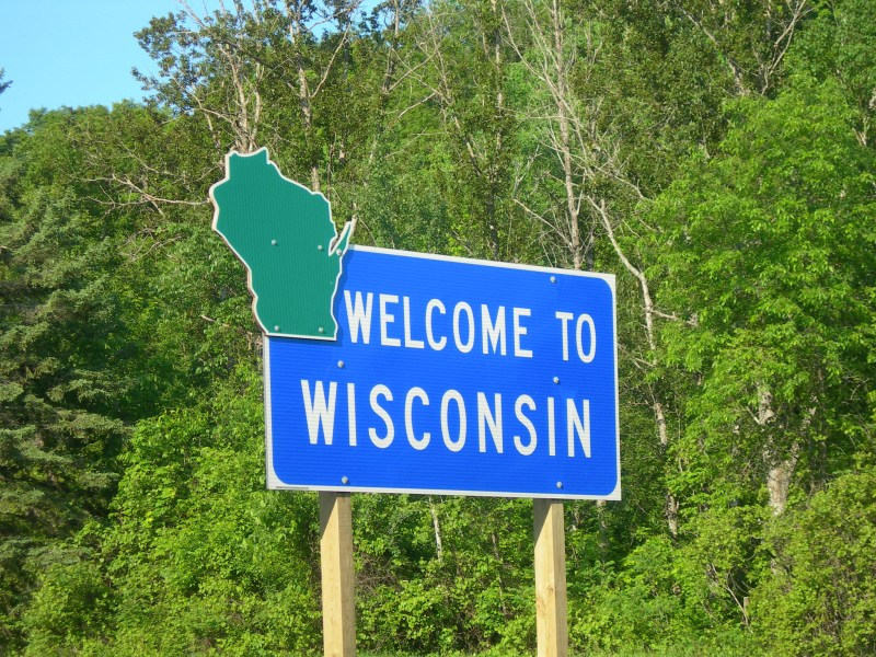 """A blue highway sign with a green state outline reads """"Welcome to Wisconsin."""""""