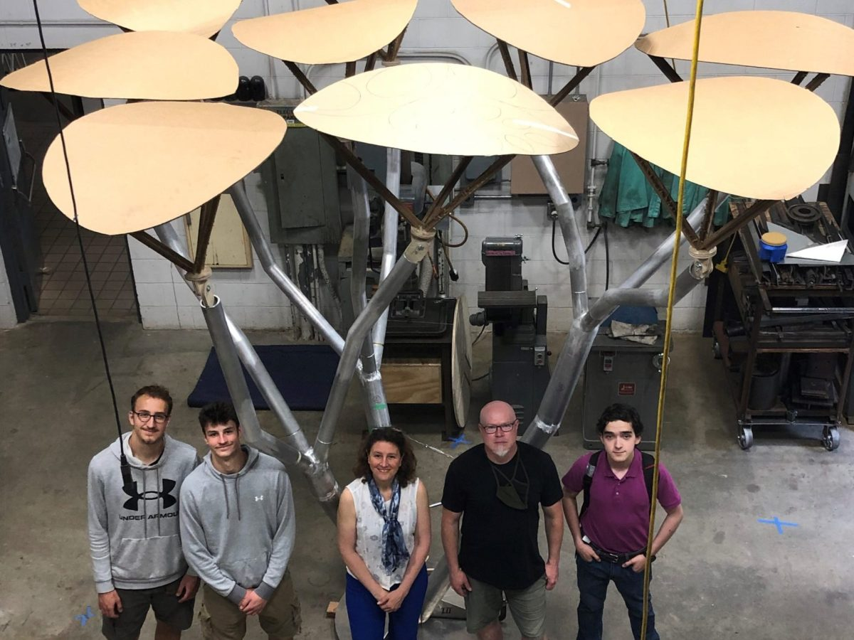 Five people stand under nine aluminum leaves that will soon be outfitted with solar panels.