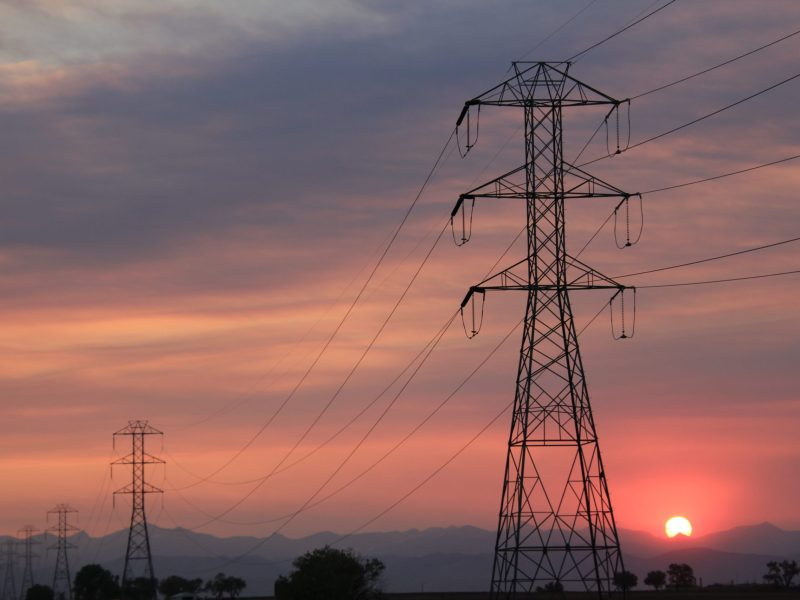 Transmission towers silhouetted against a hazy red sky during the Cameron Peak fire.