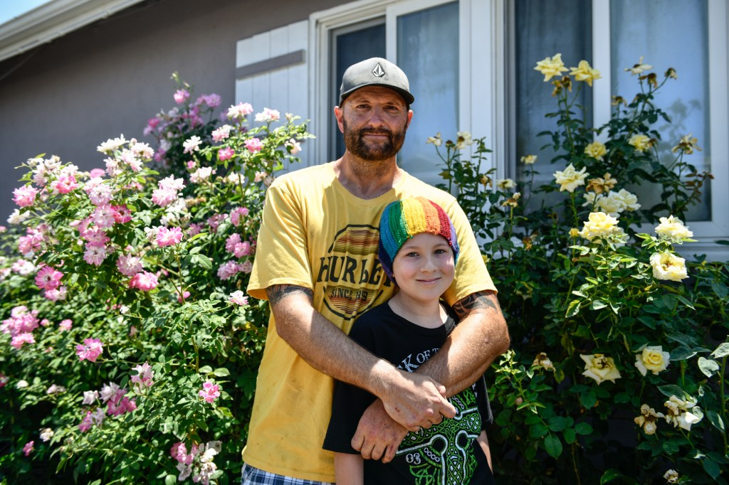 ill Hollman with his son outside of his home in the San Fernando Valley.