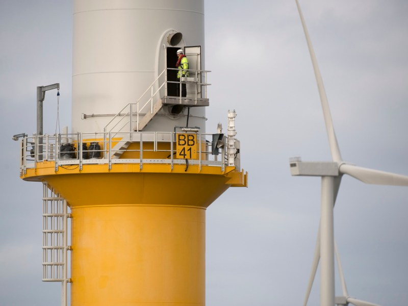 A worker on an offshore wind platform with a turbine in the background.