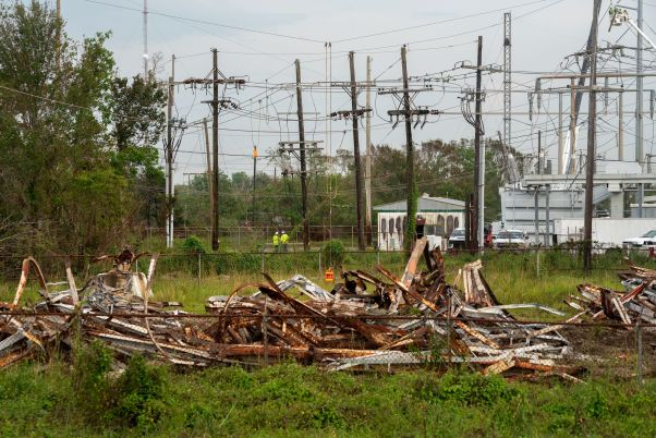 A ruined transmission line sits in a field.