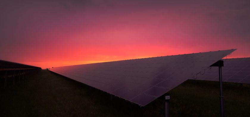 sunrise behind a solar panel