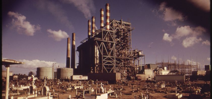 an old picture from the 1970s of a Puerto Rican power plant in the middle of a graveyard