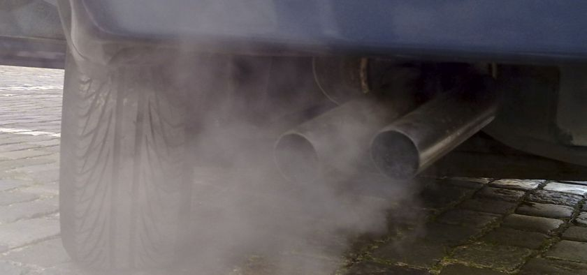 close up of car exhaust pipe with gray cloud