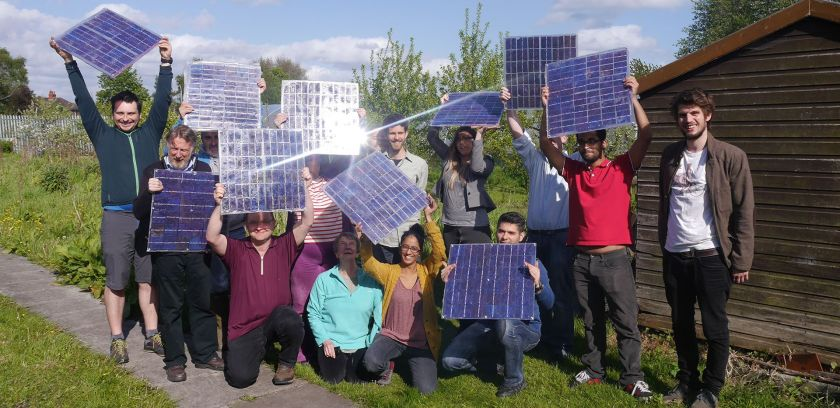 group of ten people of different ages holding solar panels up in the sunlight in a community garden