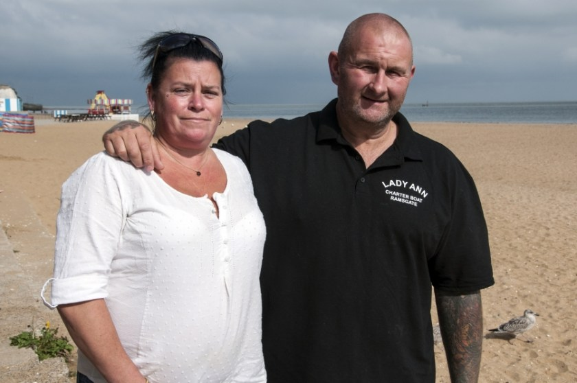 A couple standing on a beach, the man's arm around his wife's shoulder