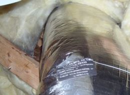 Air leakage through the duct penetration shows up because of the dirty fiberglass insulation.