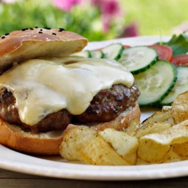 bilde av tallerken med cheeseburger , chips og grønnsaker
