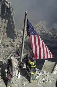© Ricky Flores. Firefighters raise a flag at the site of the World Trade Center after two passenger jet airplanes slammed into the Twin Towers during a terriost attack on the United States causing a catastrophic collaspe of the buildings on September 11, 2001 (© Ricky Flores/The Journal News)