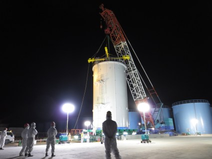 Workers at the Fukushima Daiichi nuclear power plant stand by as new storage tanks are hoisted into position.