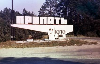 A historic photo of newlyweds posing in front of the sign for the City of Pripyat.