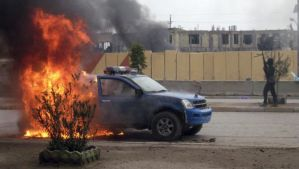 In this Wednesday, January 1, 2014, file photo, an insurgent stands guard after setting fire to an Iraqi police truck in front of the provincial government headquarters in Fallujah, Iraq. (AP Photo, File)
