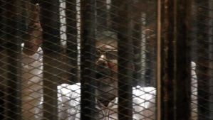Ousted Egyptian President Mohammed Morsi talks from a cage in a makeshift courtroom inside a police academy in Cairo, Egypt, 28 January 2014.