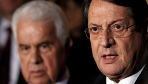 FILE - In this Monday, Nov. 25, 2013 file photo, Cyprus' president Nicos Anastasiades, right, and Turkish Cypriot leader Dervis Eroglu, left, talk to the media after their meeting in the divided capital Nicosia, Cyprus. In a brief statement Friday Feb. 7, 2014, Turkish Cypriot officials revealed that efforts to reunify the divided Mediterranean island nation of Cyprus will recommence next week after rival Greek and Turkish Cypriots agreed to a new round of talks. (AP Photo/Petros Karadjias, File)