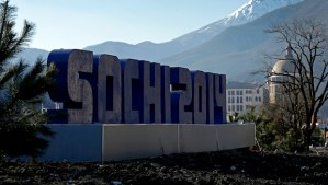 The Caucasus Mountains rise beyond a sign for the Sochi Olympics Thursday, Feb. 6, 2014, in Rosa Khutor, Russia. The area will host the alpine events at the 2014 Winter Olympics which opens Friday, Feb. 7. (AP Photo/Charlie Riedel)