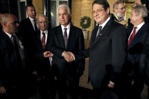 In this November 25, 2013 file photo, Cyprus president Nicos Anastasiades, right, and Turkish Cypriot leader Dervis Eroglu, left, shake hands after their meeting in the divided capital Nicosia, Cyprus. (AP Photo/Petros Karadjias, File)