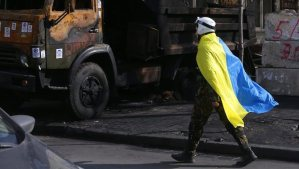 A protester covered with a Ukrainian national flag passes by a destroyed truck near the Ukrainian Parliament building in downtown of Kiev, Ukraine, on February 24, 2014. (EPA/MAXIM SHIPENKOV)