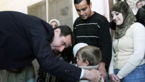 A handout picture released by the official Syrian Arab News Agency (SANA) shows Syria's President Bashar Al-Assad, left, visiting the Dweir shelter for the displaced people in the industrial city of Adra, northeast of the capital Damascus, on March 12, 2014. (AFP Photo/HO/SANA)