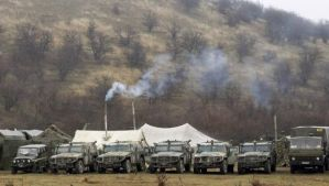Military vehicles, believed to be property of the Russian army, are seen near the territory of a Ukrainian military unit in the village of Perevalnoye, outside Simferopol, March 7, 2014. (Reuters/Vasily Fedosenko)