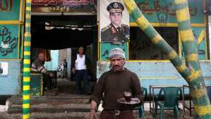 A waiter serves tea in a public cafe where a poster for Egypt's army chief, Field Marshal Abdel-Fattah El-Sisi, is hung on a wall, in Cairo on March 16, 2014. (REUTERS/Asmaa Waguih)