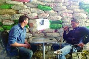 Lebanese men smoke shisha at a cafe surrounded by sandbags in Hermel, Lebanon, in early March 2014. (Asharq Al-Awsat/Hussein Darwish)