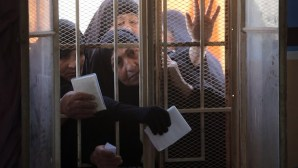 Iraqi women wait behind a window to receive their electronic voter ID cards in the capital Baghdad on February 25, 2014, ahead of legislative elections in April. (AFP PHOTO/AHMAD AL-RUBAYE)