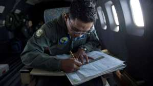 A Royal Malaysian Air Force Navigator captain, Izam Fareq Hassan works on a map onboard a Malaysian Air Force CN235 aircraft during a search and rescue (SAR) operation to find the missing Malaysia Airlines flight MH370 plane over the Strait of Malacca. (AFP PHOTO/MOHD RASFAN)