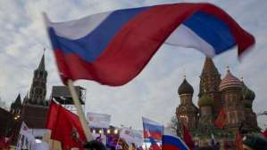 """Pro-Putin demonstrators wave Russian national flags as they gather towards to Red Square in Moscow, Russia, Friday, March 7, 2014, with Spassky Tower, left, and St. Basile Cathedral, right, are in the background. Russia rallied support Friday for a Crimean bid to secede from Ukraine, with a leader of Russia's parliament assuring her Crimean counterpart that the region would be welcomed as """"an absolutely equal subject of the Russian Federation."""" Across Red Square, 65,000 people waved Russian flags, chanting """"Crimea is Russia!""""(AP Photo/Alexander Zemlianichenko) Management"""