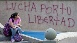 epa04135625 A woman sits in front of a graffitti saying: 'Fight for your freedom' during a demonstration against the Venezuelan government of Nicolás Maduro at Altamira square in Caracas, Venezuela, on March 21, 2014. (EPA/SANTI DONAIRE)