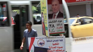 An Iraqi man walks past campaign posters as he walks on a street in the capital, Baghdad, on April 29, 2014, one day ahead of Iraq's first general election since US troops withdrew. (AFP PHOTO / ALI AL-SAADI)
