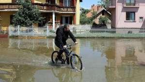 A man rides a bicycle through flooded streets of Svilajnac, 120 kilometers south of Belgrade, on May 20, 2014. (AFP PHOTO / SASA DJORDJEVIC)