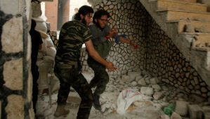 A Free Syrian Army fighter helps his wounded fellow fighter in Al-Amariya district in Aleppo on May 8, 2014. (REUTERS/Ammar Abdullah)