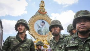 Thai soldiers gather under a portrait of King Bhumibol Adulyadej after anti-government protesters were removed off the site following the coup declared at Democracy Monument in Bangkok, Thailand, on May 23, 2014. (EPA/DIEGO AZUBEL)
